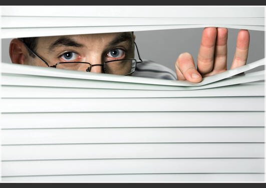 Close-up of venetian blind with male looking out of it, Stock image