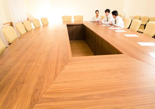 Tre menneske sit ved bord.