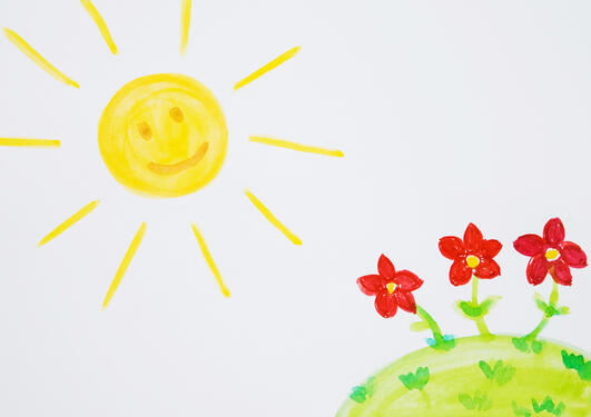 Children's drawing of the sun overshining a field with three red flowers