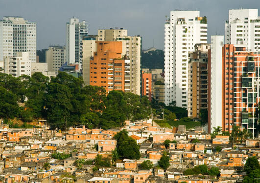 Skyscrapers in Sao Paulo city contrasting with favela shanty town of Morumbi neighborhood in foreground, Brazil.