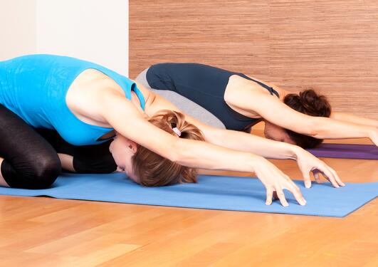 Bildet viser to personer som trener yoga.