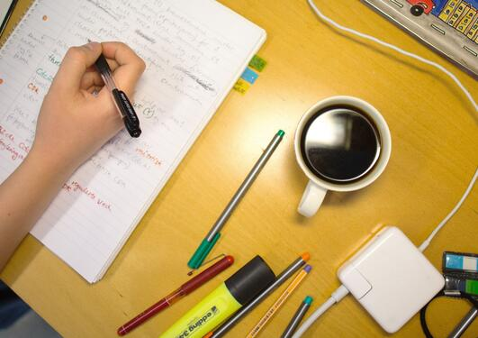Desk, hand, coffee cup, pens and pencils