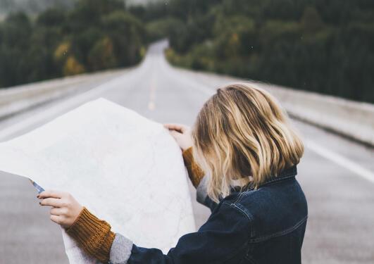 Kvinne står på veien og studerer et kart