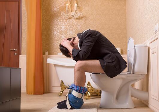 Ung mann på toalettet