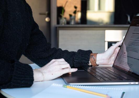 Bilde av hender som jobber med en pc.