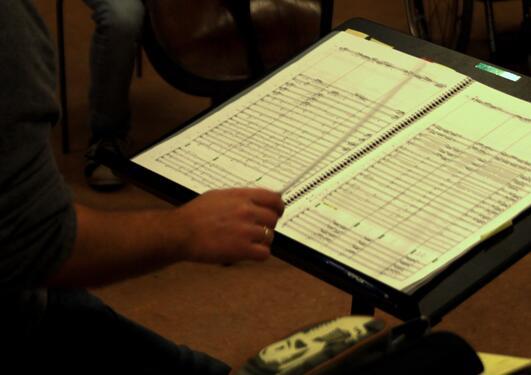 Illustrasjonsfoto med hånd som dirigerer og partitur på notestativ