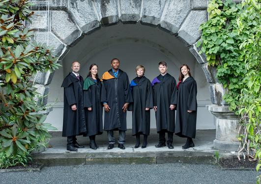 seks doktorer iført seremonikapper i muséhagen