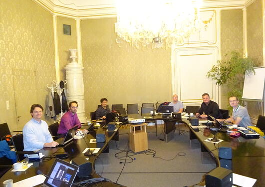 A group of people in a posh meeting room