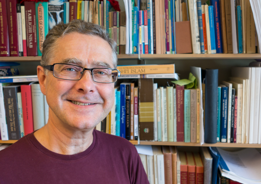 Richard Natvig framfor ei bokhylle med bøker.