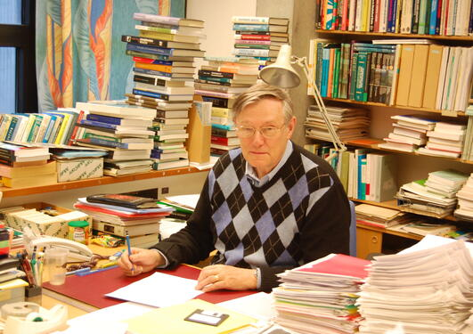 John in his office surrounded by books and papers of work in progress