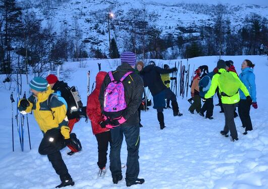 People in ski clothes practising balancing on one foot