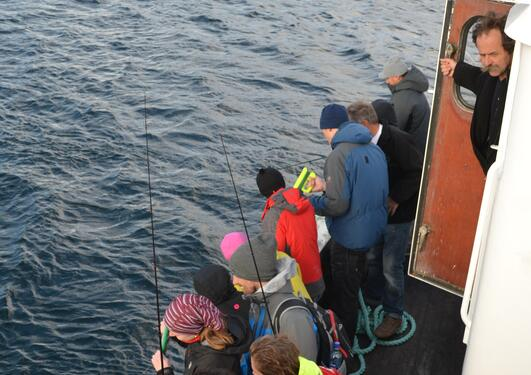 """People standing close to eachother and fishing on board """"Havegga"""""""