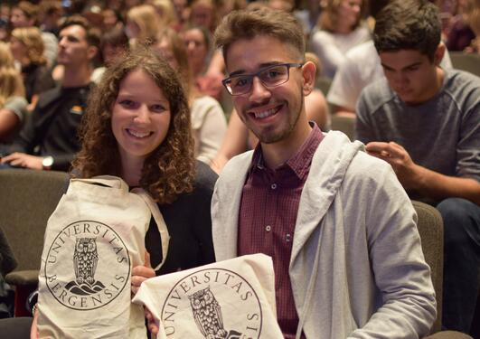 Two students smiling, facing the camera, holding a UiB tote bag