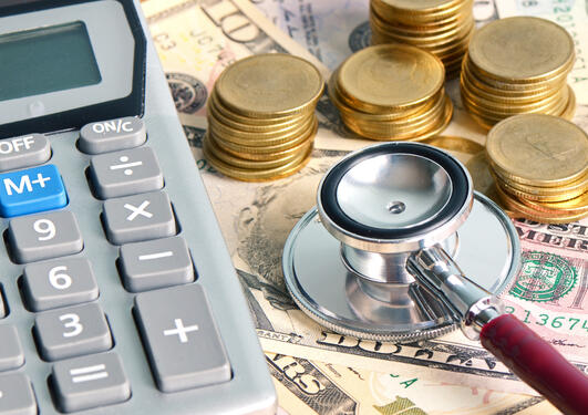 photo showing calculator, money and stetoscope
