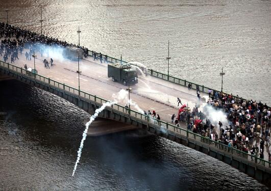 A picture of a confrontation between protestors and riot police on a bridge in Egypt during the Arab spring, which began in December 2010.