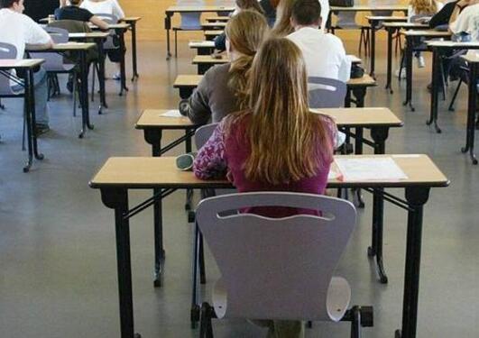 Studenter sitter ved hver sin pult i et eksamenslokale og venter