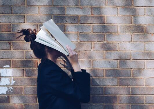 Student in front of natural rustic red brick background holding book up to her face.