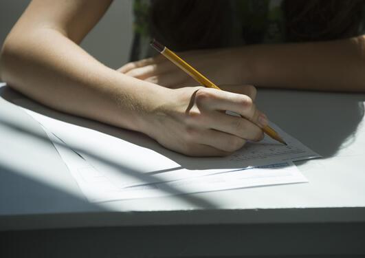 En student skriver med blyant