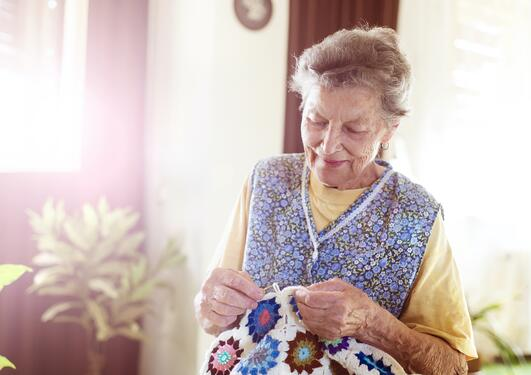 Eldre dame som strikker.
