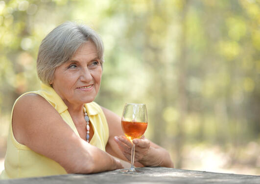 Eldre kvinne ute i naturen med vinglass