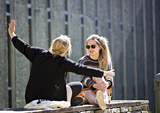 To jenter sitter utenfor UB og prater. Høstfarger i bakgrunnen.