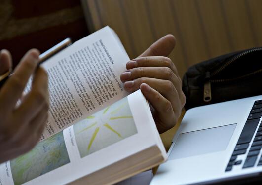 Nærbilde av hender som holder en bok foran en PC