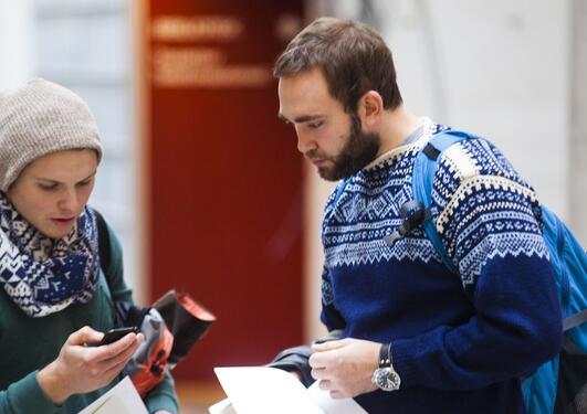 To mannlige studenter ser på en mobil