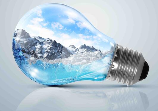 Stock photo image of light bulb with mountain landscape pictured inside the bulb; indicating the link between energy consumption and environmental issues.