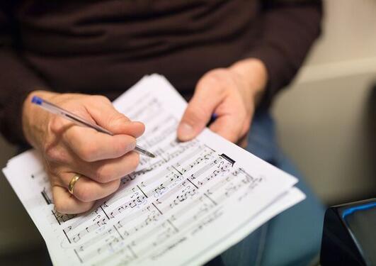 Nærbilde av noteark og hånd med penn.