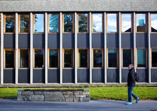HF-biblioteket fra siden med benkene, gående mann