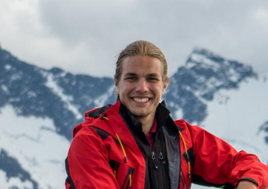Portrait of Erik Kusch with a snowy mountain backdrop