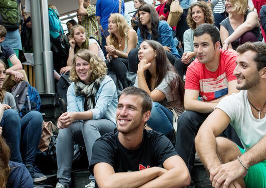 En del studenter som sitter tett i tett i en trapp