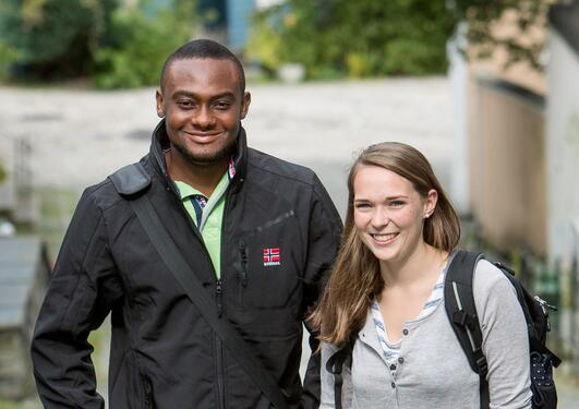 A male and female student looking at kamera smiling, outside