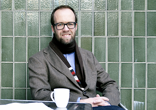 Espen Gamlund sitter på kafe, fingrene i kors, kaffekopp ved siden av seg