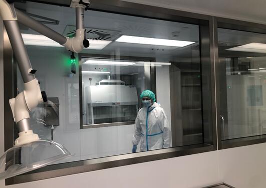 vi ser en person ikledd labutstyr, maske og hårnett i et rom. En maskin er i forgrunnen. Glassvinduer
