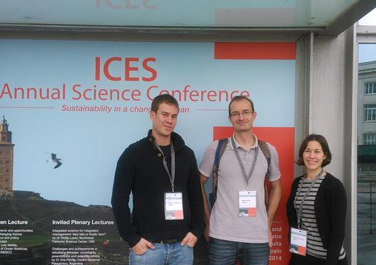 Fabian, Mikko and Bea posing in front of the conference poster