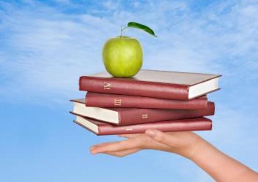 En hånd holder fire bøker med et eple på toppen