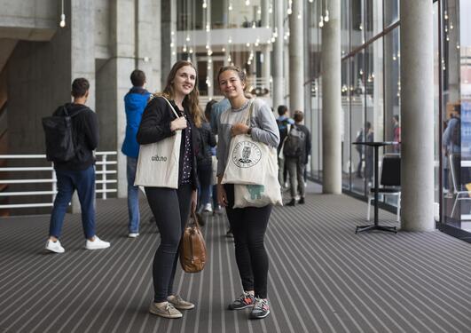 Portrett av to kvinnelige studenter i Grieghallen som har hvert sitt UiB-nett over armen