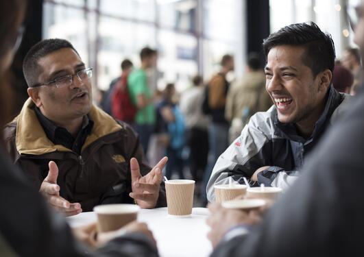 Mannlige studenter i samtale rundt et bord