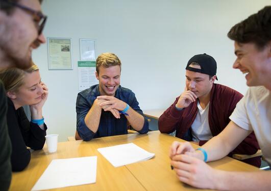 Gruppe med studenter som sitter rundt et bord