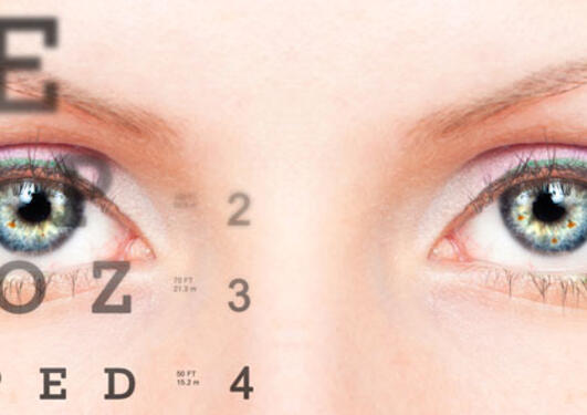 closeup of eyes and reading chart at the eye doctor's office.