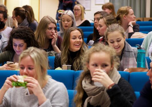 Studenter snakker og spiser i Stort auditorium på SV-bygget.