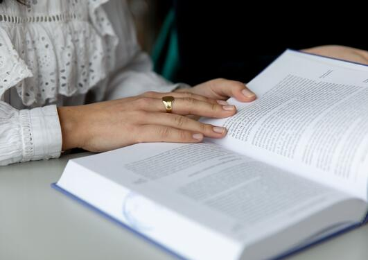 To hender holder åpen en lærebok