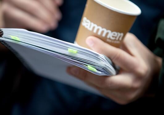 Nærbilde av papirkopp og en bunke papirer