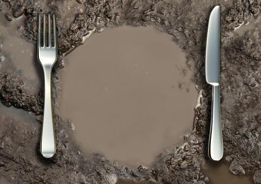Kniv og gaffel i sølv lagt på en imiaginær middagstallerken laget i gjørme