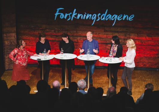 forskere som deltar i en debatt på en scene