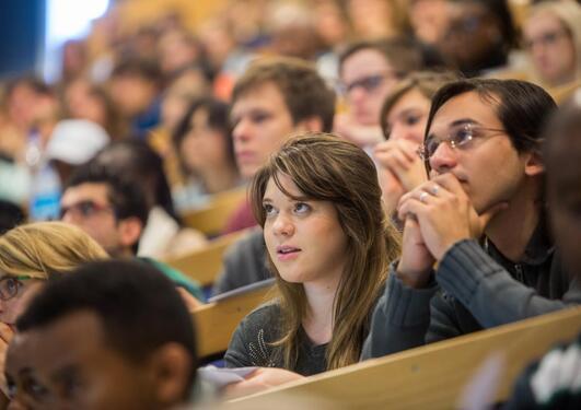 Studenter følger med på foreleser i et fullt auditorium.