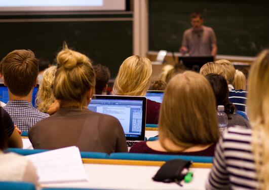 Studenter i et auditorium følger med på foreleseren.