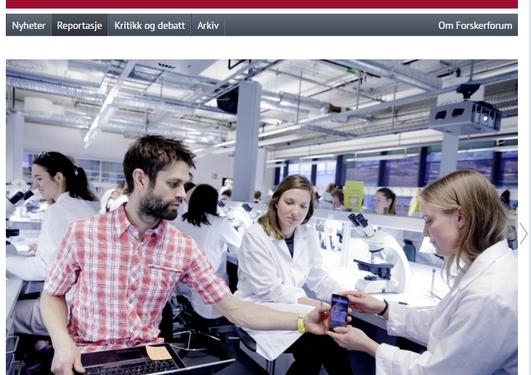 Christian B. Jørgensen ser på mobil og dataskjerm saman med studentar i eit laboratorium.