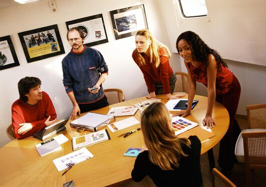 Unge mennesker i en møtesituasjon som diskuterer, delvis stående